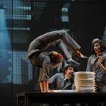 Szene aus der Show Cirkopolis: Frau macht Handstand auf einem Tisch mit einem Stapel Unterlagen. Im Hintergrund zwei weitere Artisten und eine Industriehalle als Kulisse