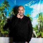 Musiker und Kabarettist Hannes Ringlstetter for einer Tapete mit tropischen Strand