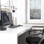 Weißer Schreibtisch mit Monitor und Telefonen sowie einem Drehstuhl. Im Hintergrund ein Fenster