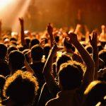 Konzertpublikum vor eine Bühne. Die Besucher trinken Bier und halten die Arme hoch.
