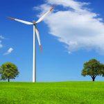 Windrad auf einer grünen Wiese mit zwei Bäumen. Der Himmel ist blau mit weißen Wolken.