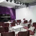 Kleinkunstbühne mit Klavier und einem purpurfarbenen Vorhang. Davorstehen einzelne moderne Stühle mit kleinen Beistelltischen