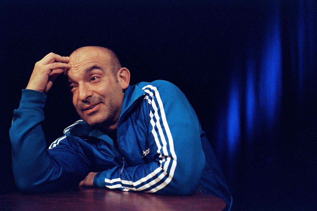 Kabarettist Django Asül lehnt auf einem Stehttisch und denkt nach