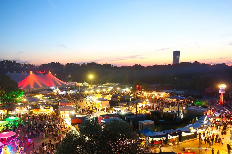 Ein Blick vom Olympiaberg über das festlich beleuchtete Tollwood Sommerfestival hinüber zum o2 Hochhaus