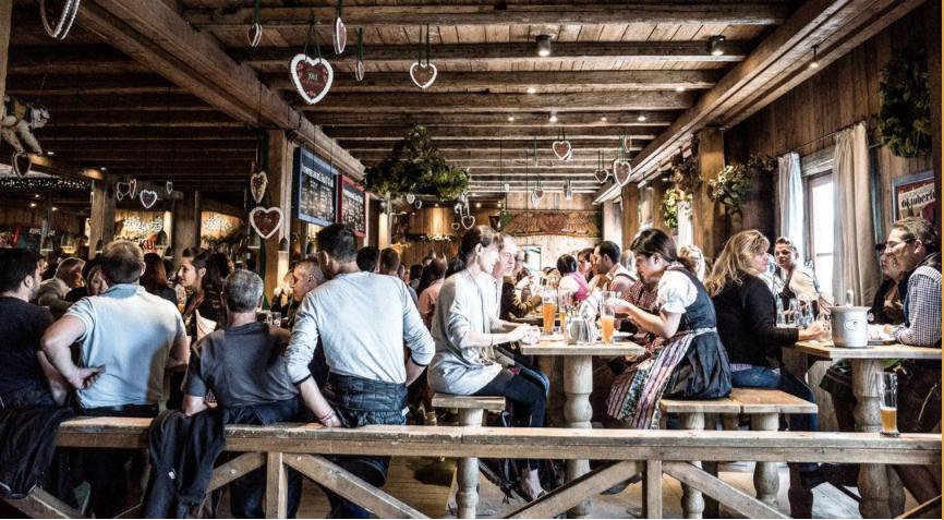 Oktoberfest Company Reservation - Tische mit Oktoberfestbesuchern rund um die Sektbar in Kufflers Weinzelt.