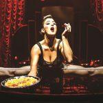 Ein Show-Girl vollzieht auf Tollwood einen Spagat auf einer Querstange und serviert dabei Süßigkeiten auf einem Tablet