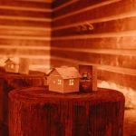 Deine Tollwood Weihnachtsfeier 2020 mit beleuchteten kleine Hexenhäuschen als Dekoration auf Stehtischen aus Holzstämmen