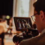Auf einem Corporate Event dreht ein Kameramann. Im Vorschaubildschirm der Kamera sind Konferenzteilnehmer im Gespräch zu sehen.