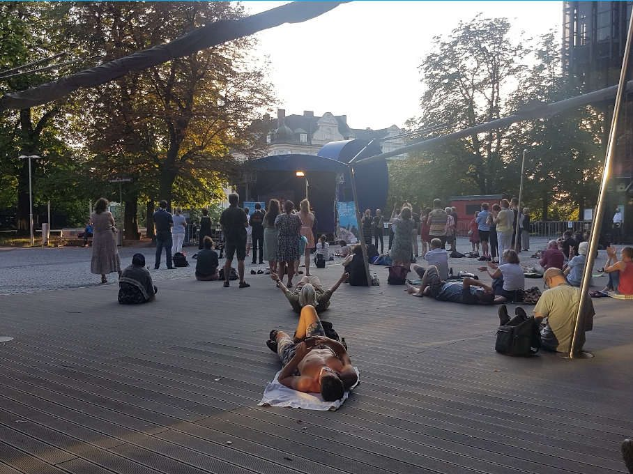 Open Air Bühne Gasteig: Zu sehen ist das Publikum vor der Bühne, welches den Mindestabstand einählt