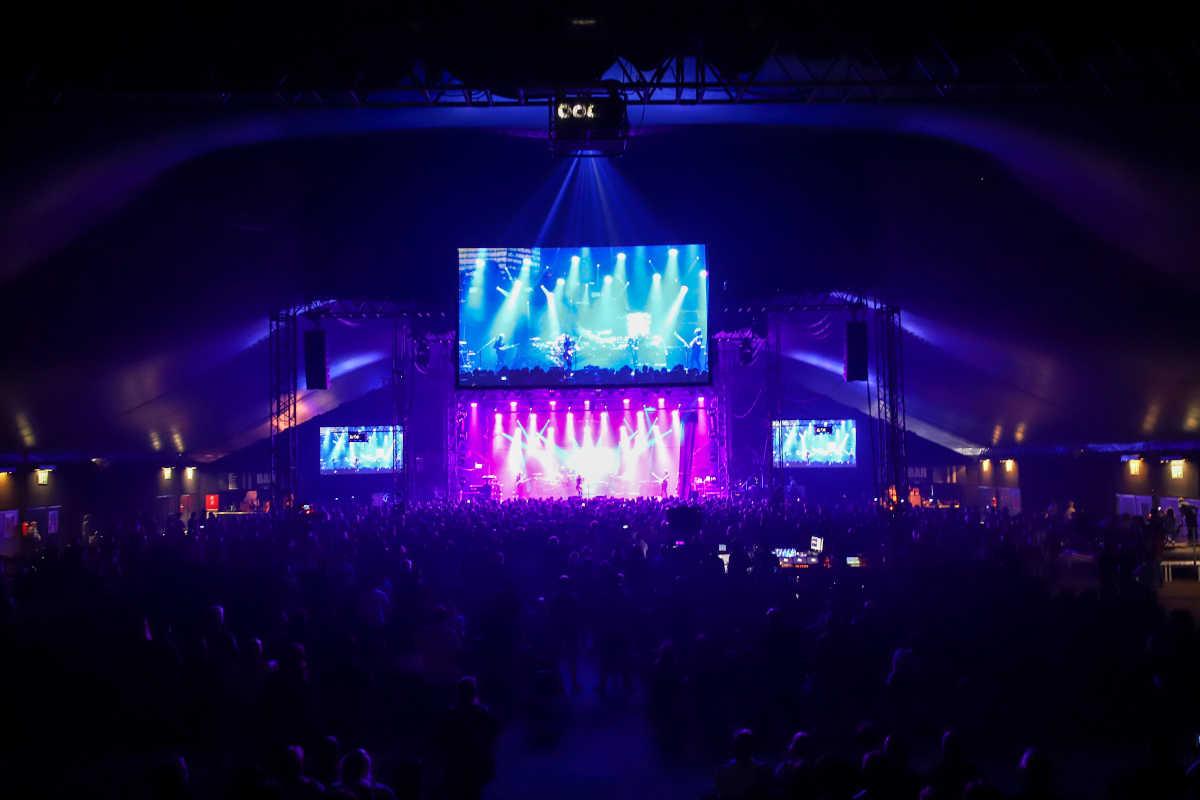 Ausbildung zum Veranstaltungskaufmann 2020, das Foto zeigt ein volles Konzertzelt mit Blick auf die Bühne und große LED-Leinwände